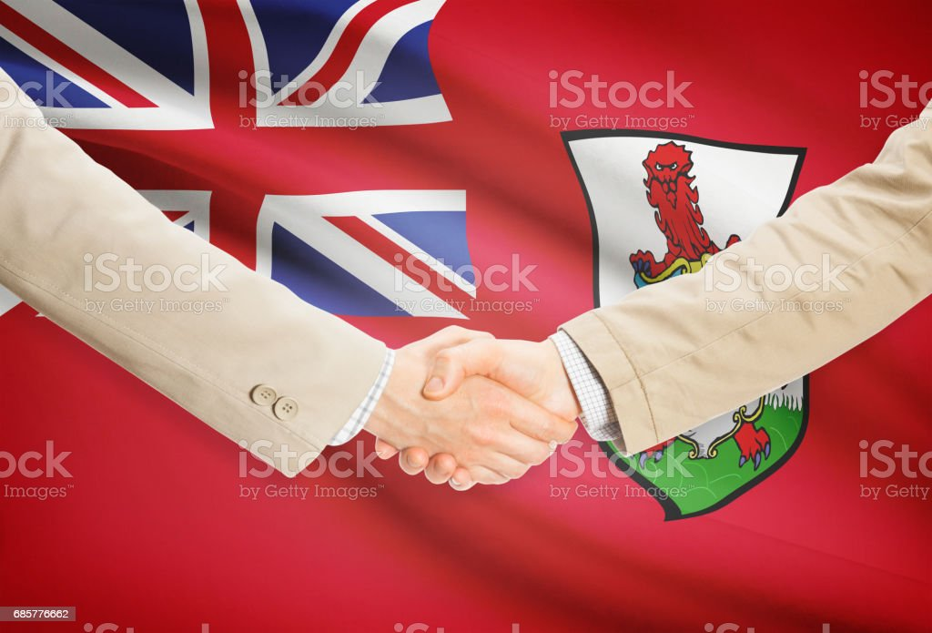 Businessmen handshake with flag on background - Bermuda royalty-free stock photo