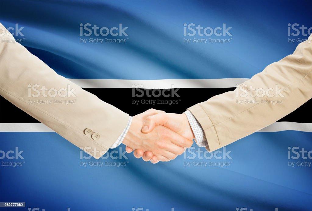Businessmen handshake with flag on background - Botswana royalty-free stock photo