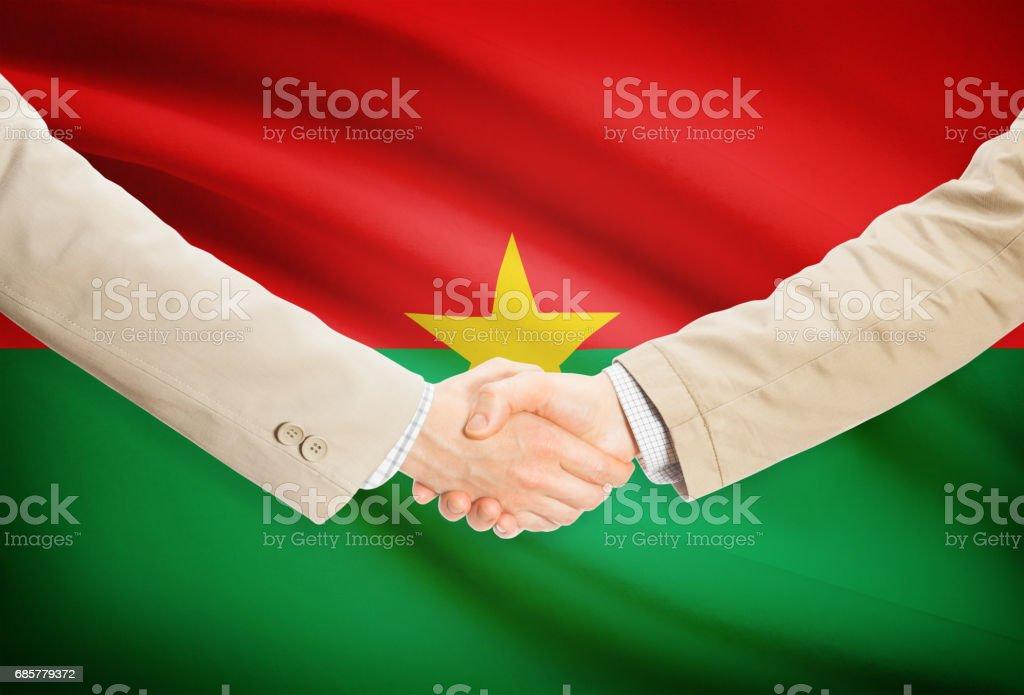 Businessmen handshake with flag on background - Burkina Faso photo libre de droits