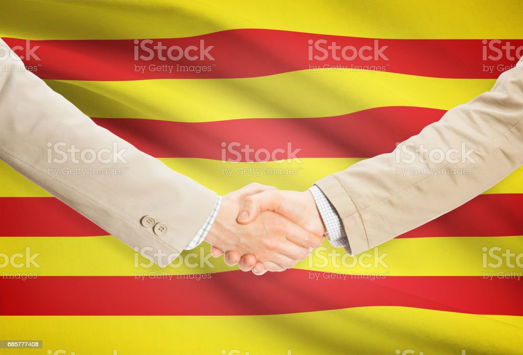 Businessmen handshake with flag on background - Catalonia - Spain royalty-free stock photo