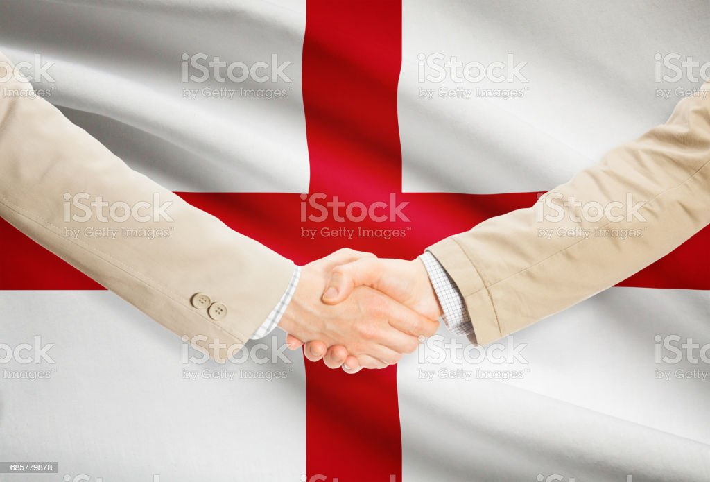 Businessmen handshake with flag on background - England royalty-free stock photo