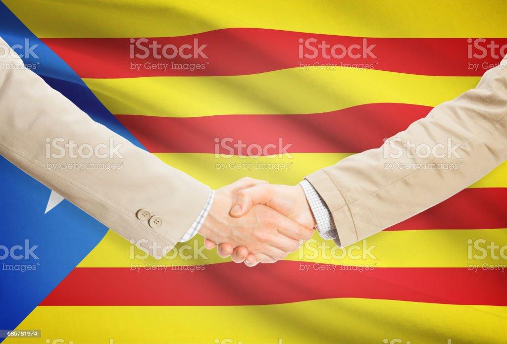 Businessmen handshake with flag on background - Estelada - Spain royalty-free stock photo