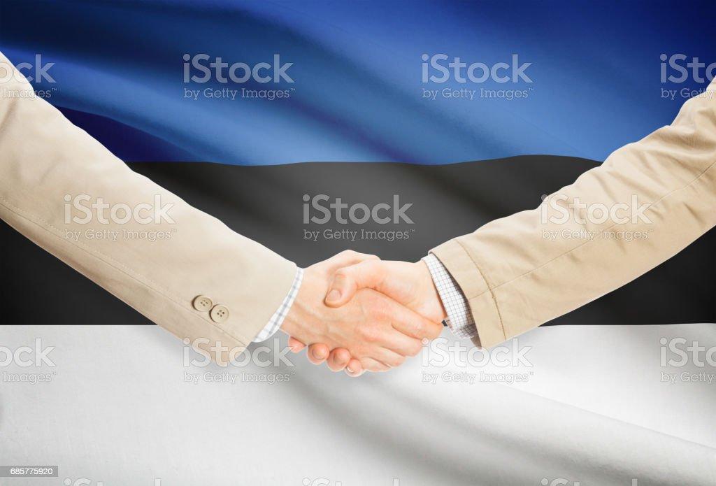 Businessmen handshake with flag on background - Estonia royalty-free stock photo