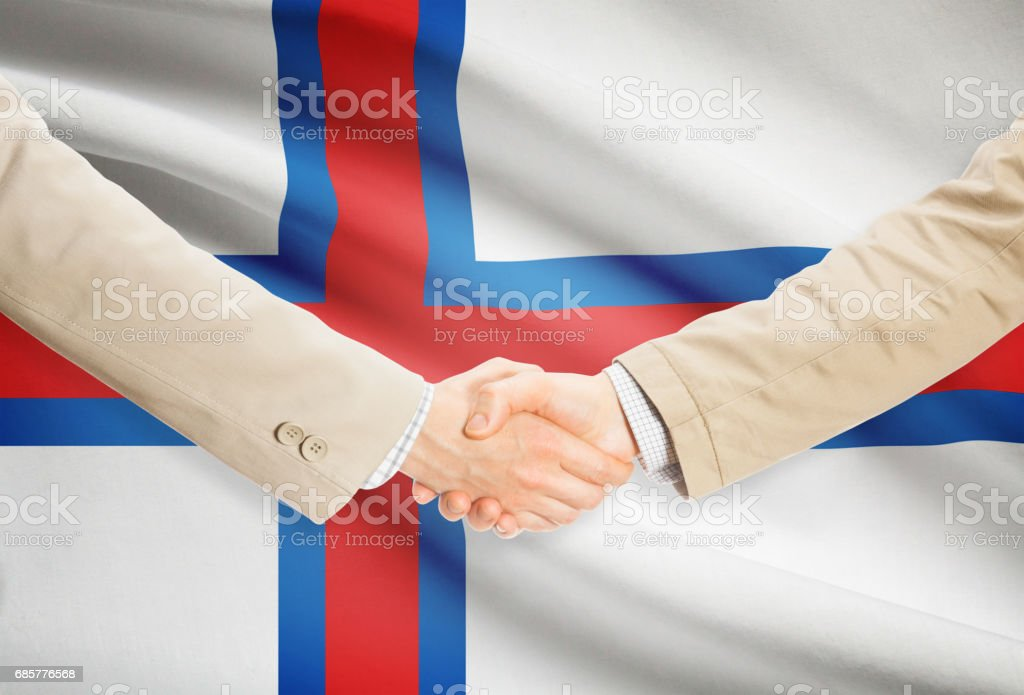 Businessmen handshake with flag on background - Faroe Islands royalty-free stock photo