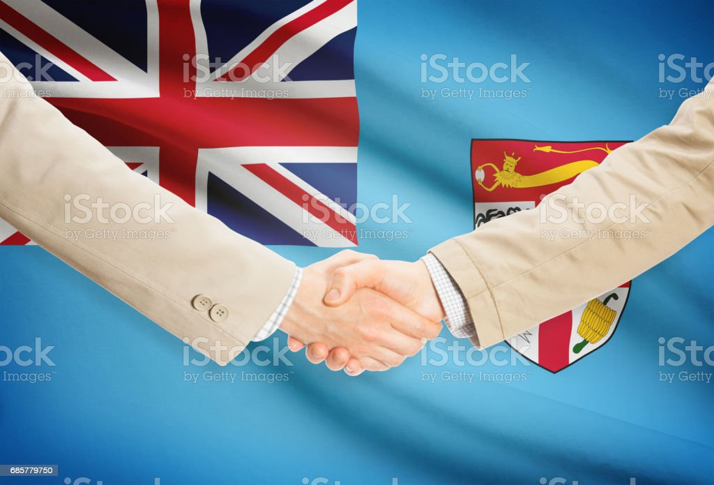 Businessmen handshake with flag on background - Fiji photo libre de droits
