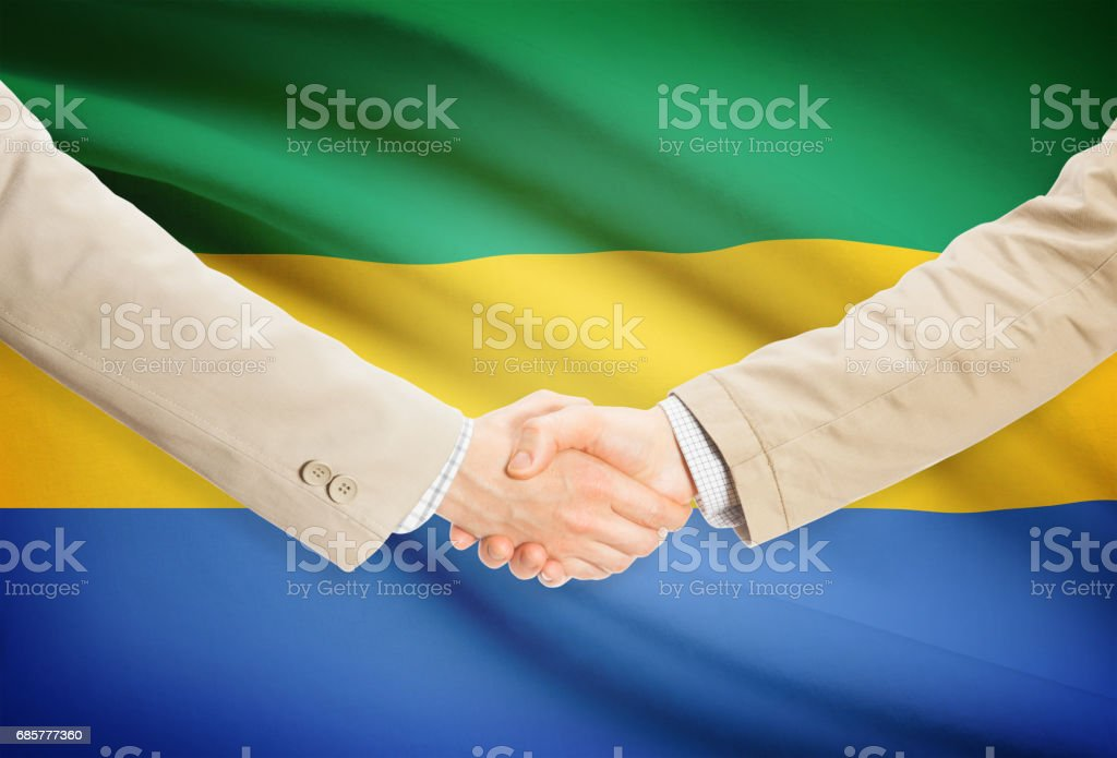 Businessmen handshake with flag on background - Gabon royalty-free stock photo