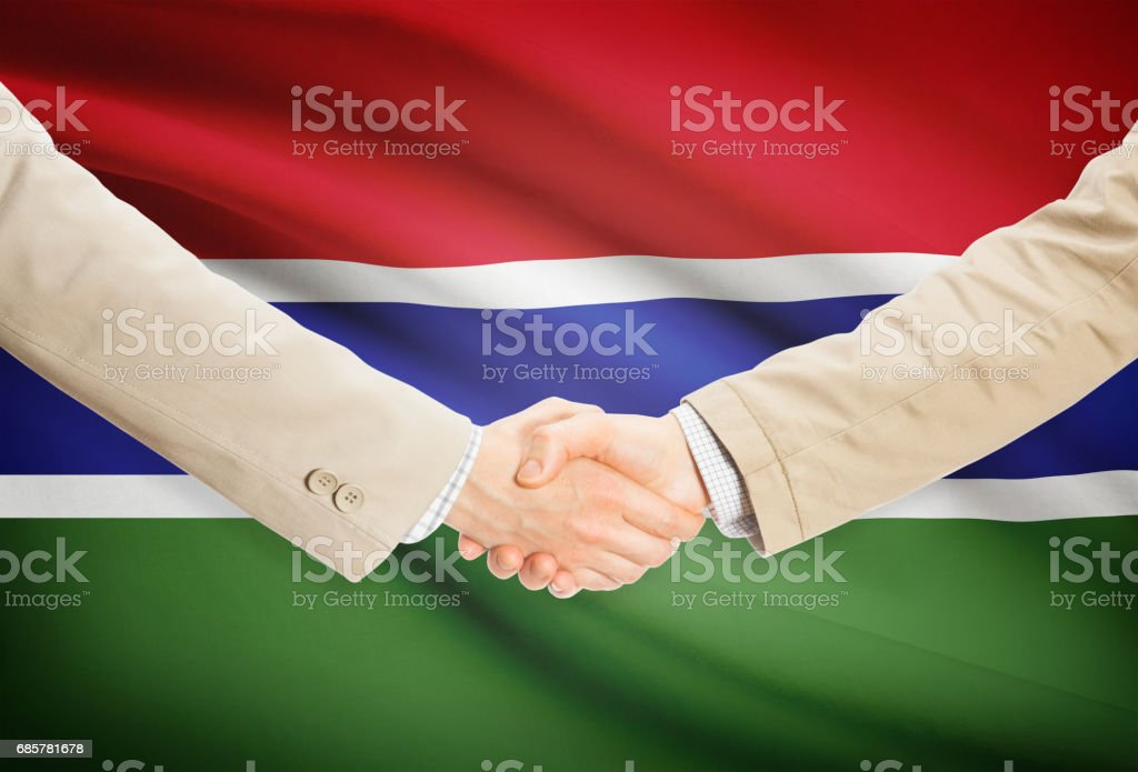Businessmen handshake with flag on background - Gambia royalty-free stock photo
