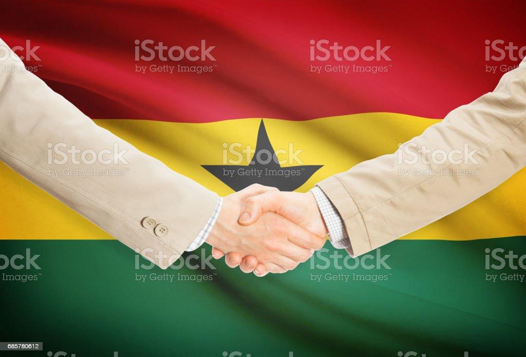 Businessmen handshake with flag on background - Ghana royalty-free stock photo