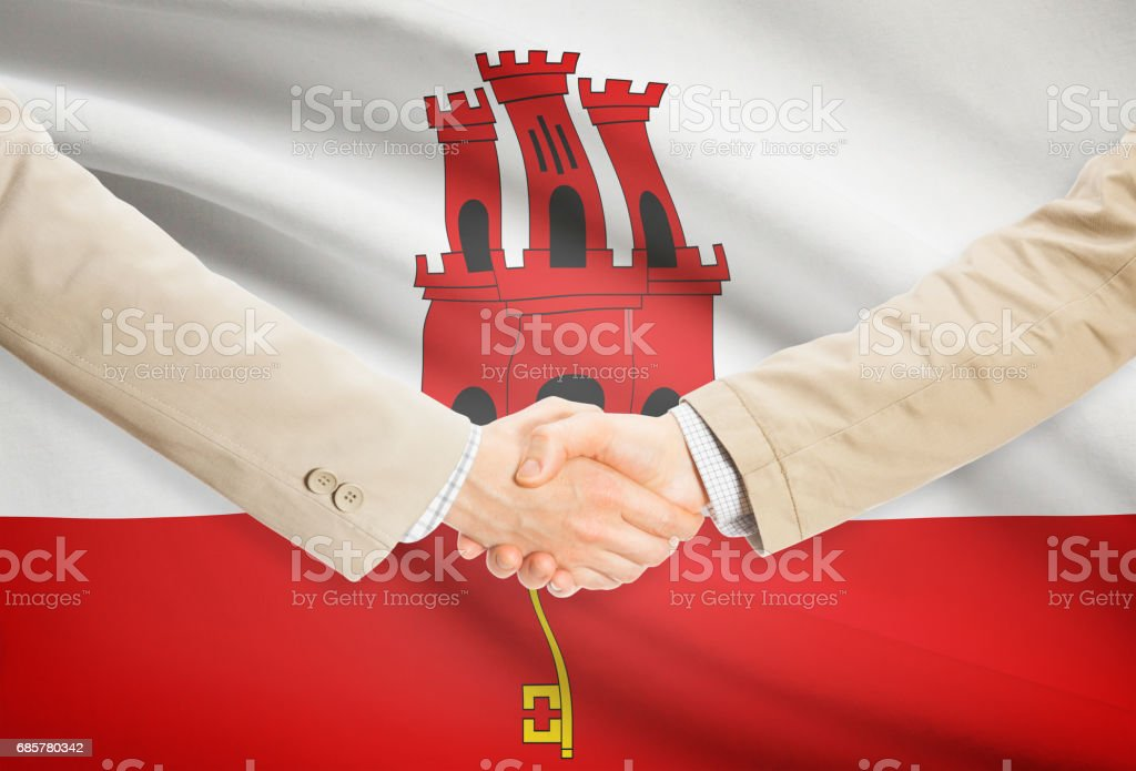 Businessmen handshake with flag on background - Gibraltar royalty-free stock photo