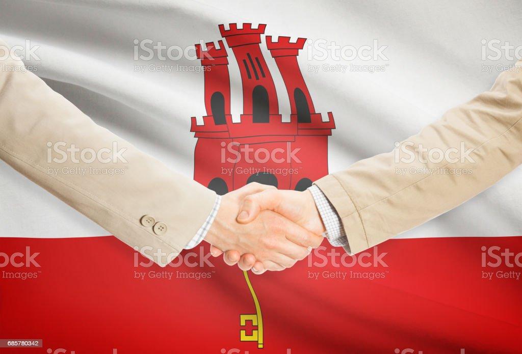 Businessmen handshake with flag on background - Gibraltar 免版稅 stock photo