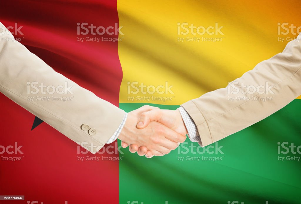 Businessmen handshake with flag on background - Guinea-Bissau royalty-free stock photo