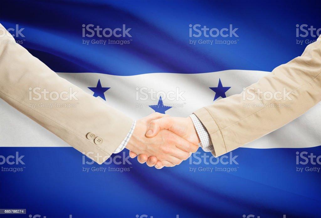 Businessmen handshake with flag on background - Honduras royalty-free stock photo