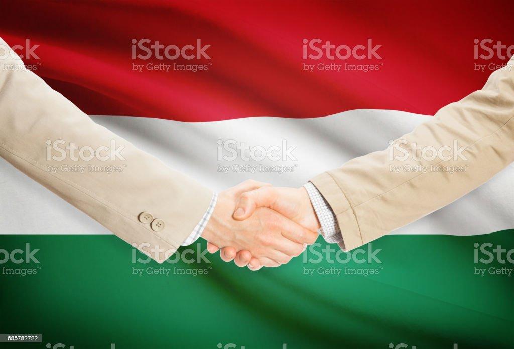 Businessmen handshake with flag on background - Hungary royalty-free stock photo