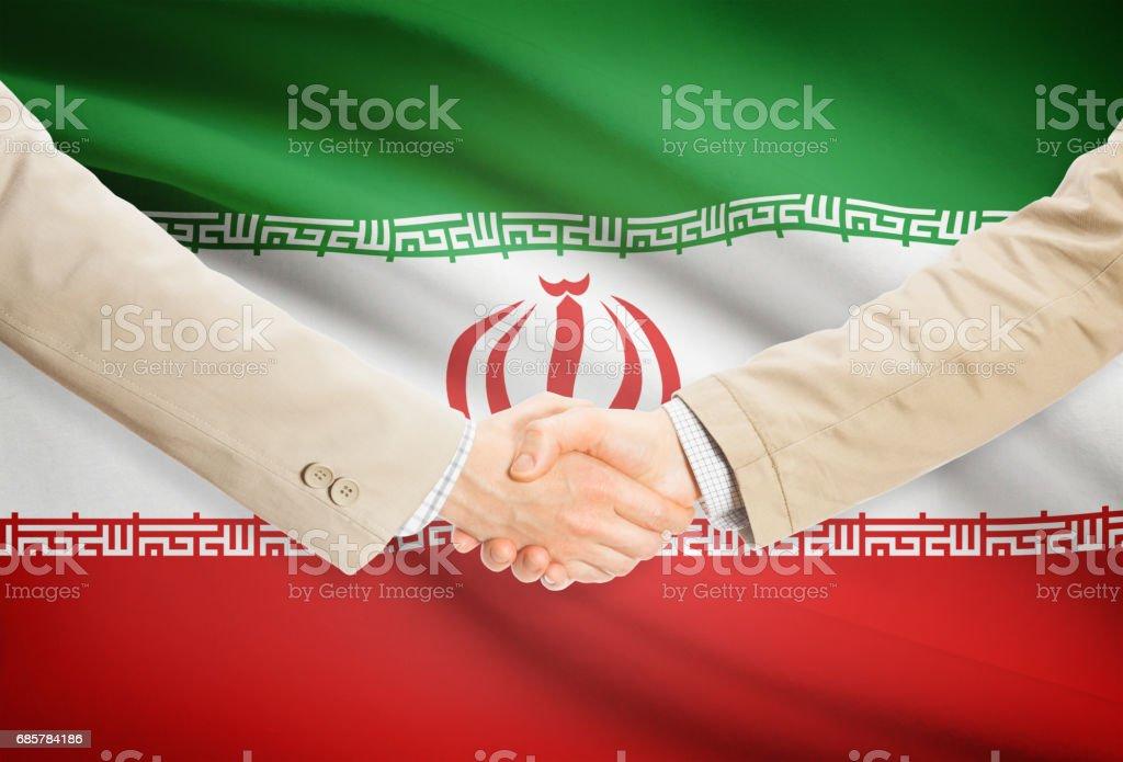 Businessmen handshake with flag on background - Iran royalty-free stock photo
