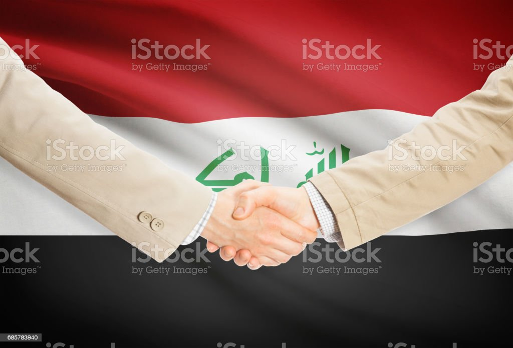 Businessmen handshake with flag on background - Iraq royalty-free stock photo