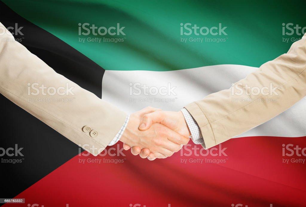 Businessmen handshake with flag on background - Kuwait royalty-free stock photo