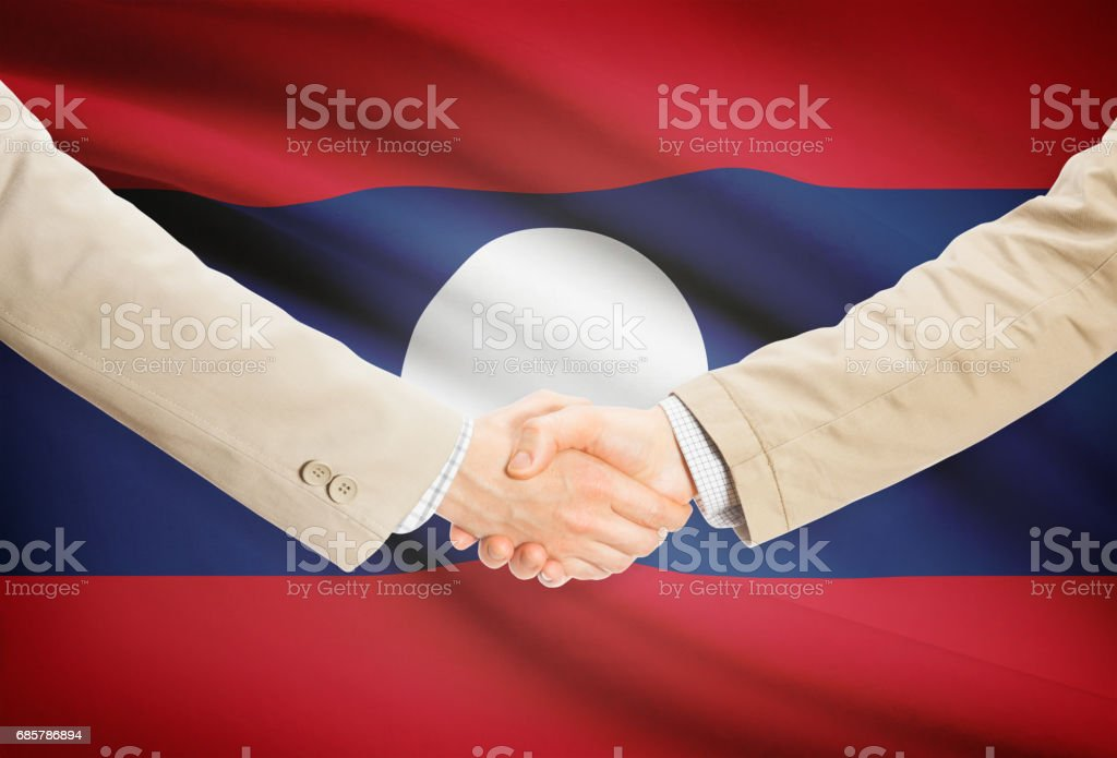 Businessmen handshake with flag on background - Laos royalty-free stock photo