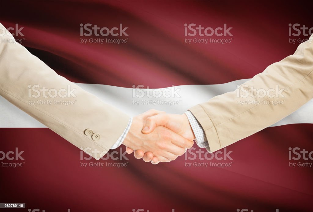 Businessmen handshake with flag on background - Latvia foto de stock libre de derechos