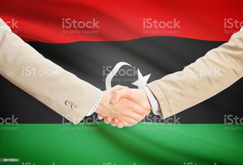 Businessmen handshake with flag on background - Libya royalty-free stock photo