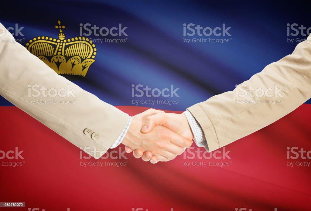 Businessmen handshake with flag on background - Liechtenstein royalty-free stock photo