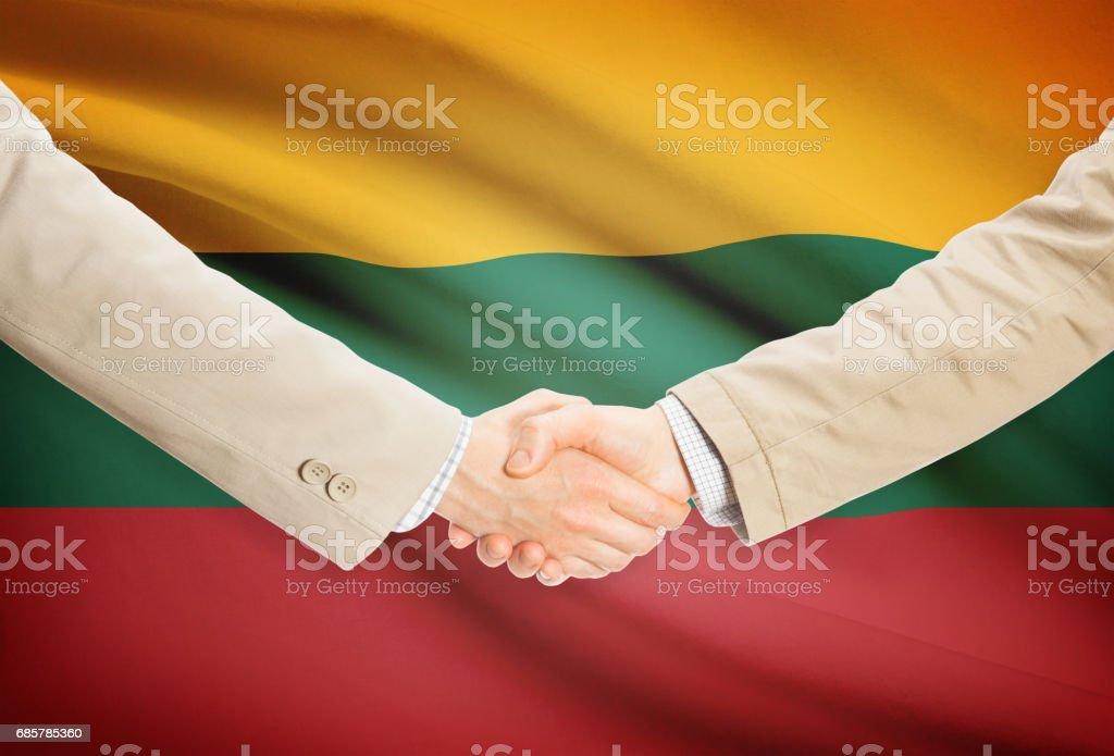 Businessmen handshake with flag on background - Lithuania Стоковые фото Стоковая фотография
