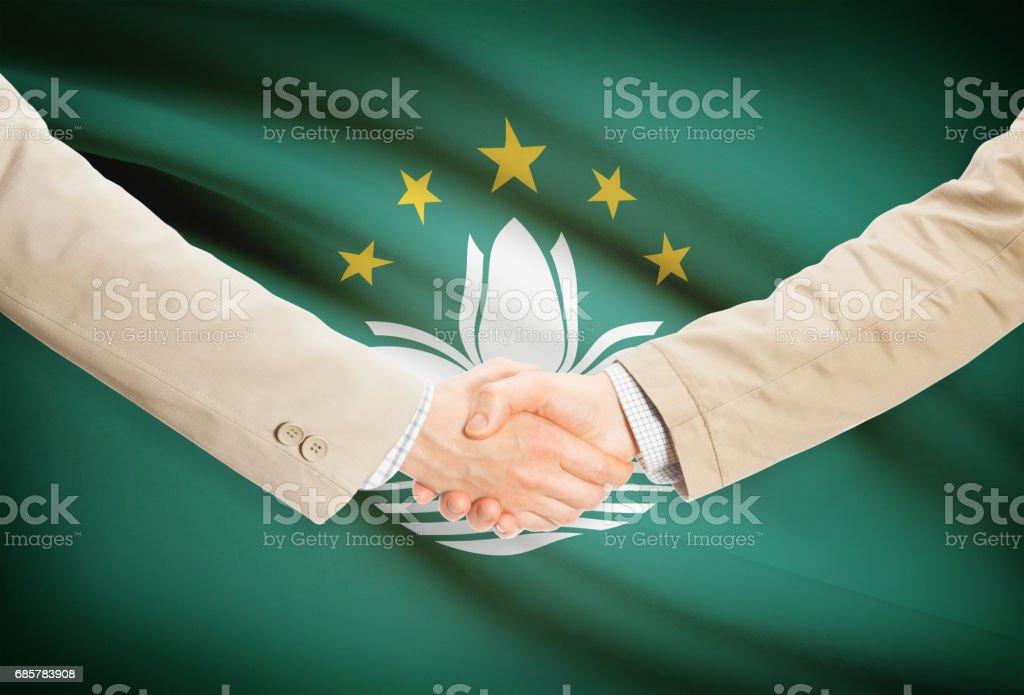 Businessmen handshake with flag on background - Macau royalty-free stock photo