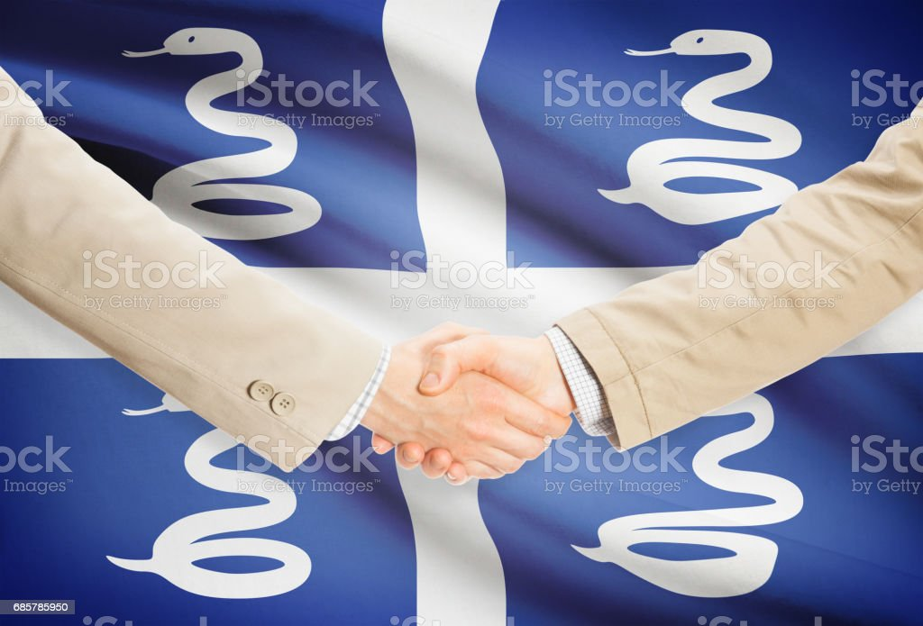 Businessmen handshake with flag on background - Martinique royalty-free stock photo