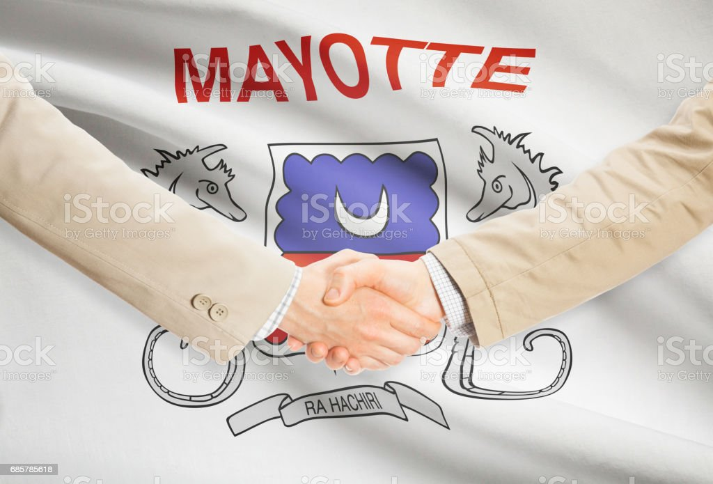 Businessmen handshake with flag on background - Mayotte royalty-free stock photo