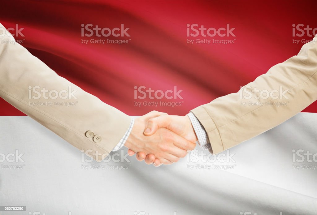 Businessmen handshake with flag on background - Monaco royalty-free stock photo