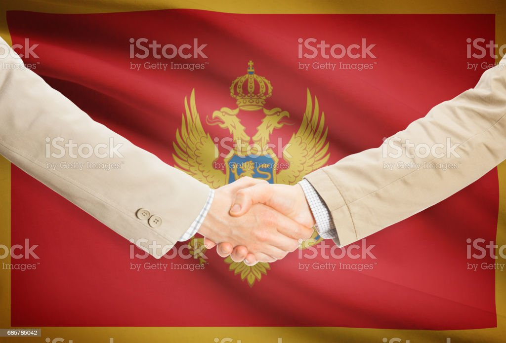 Businessmen handshake with flag on background - Montenegro foto de stock libre de derechos