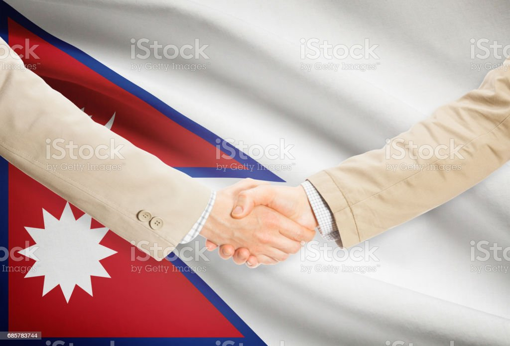 Businessmen handshake with flag on background - Nepal photo libre de droits
