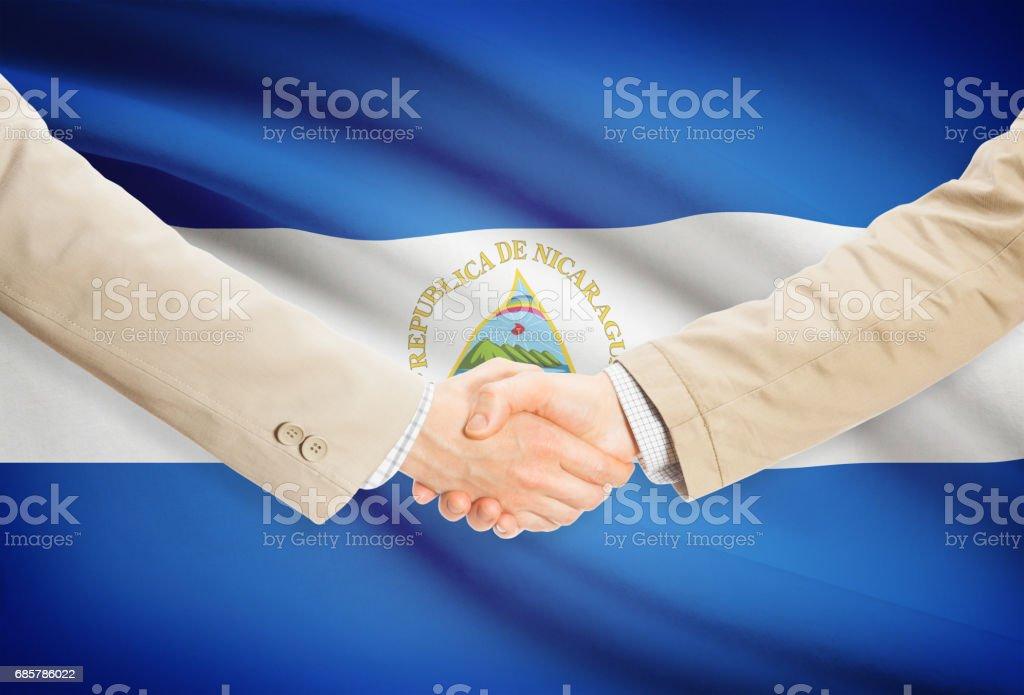 Apretón de manos de empresarios con bandera en fondo-Nicaragua - foto de stock