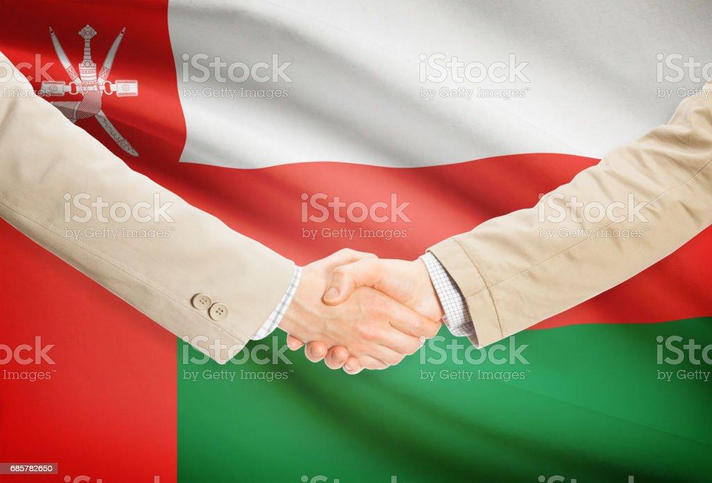 Businessmen handshake with flag on background - Oman photo libre de droits