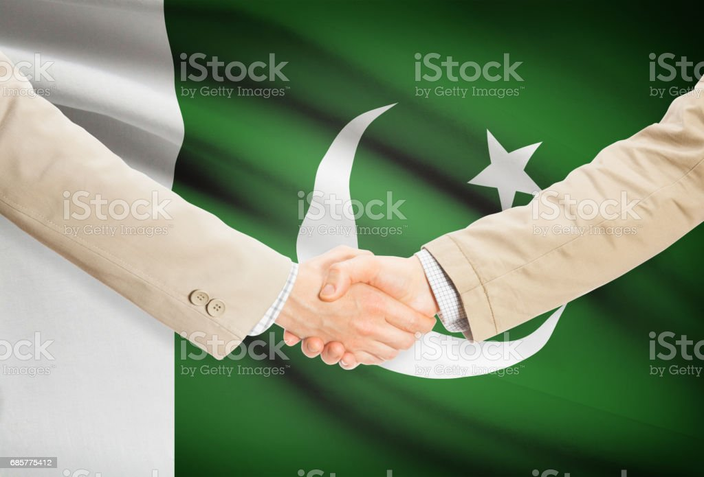 Businessmen handshake with flag on background - Pakistan royalty-free stock photo