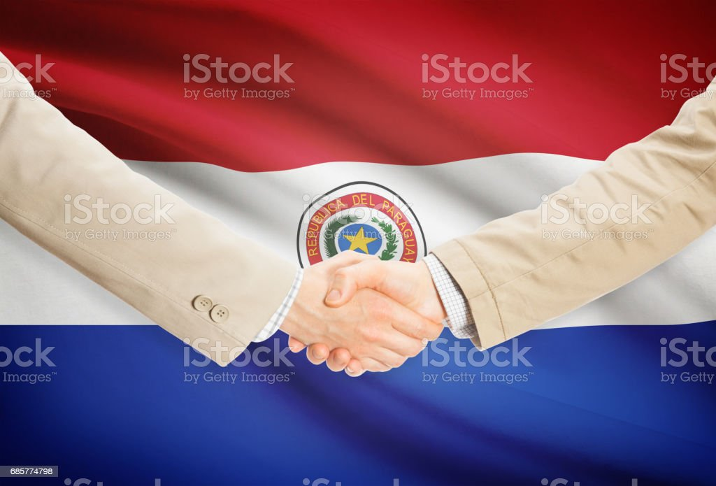 Businessmen handshake with flag on background - Paraguay royalty-free stock photo