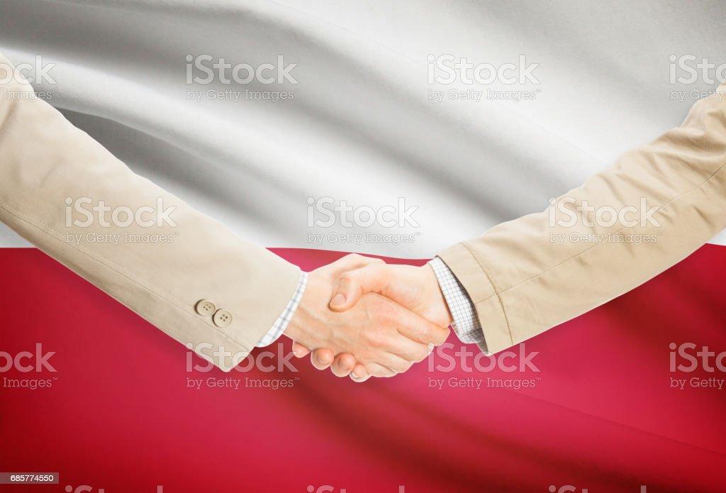 Businessmen handshake with flag on background - Poland royalty-free stock photo