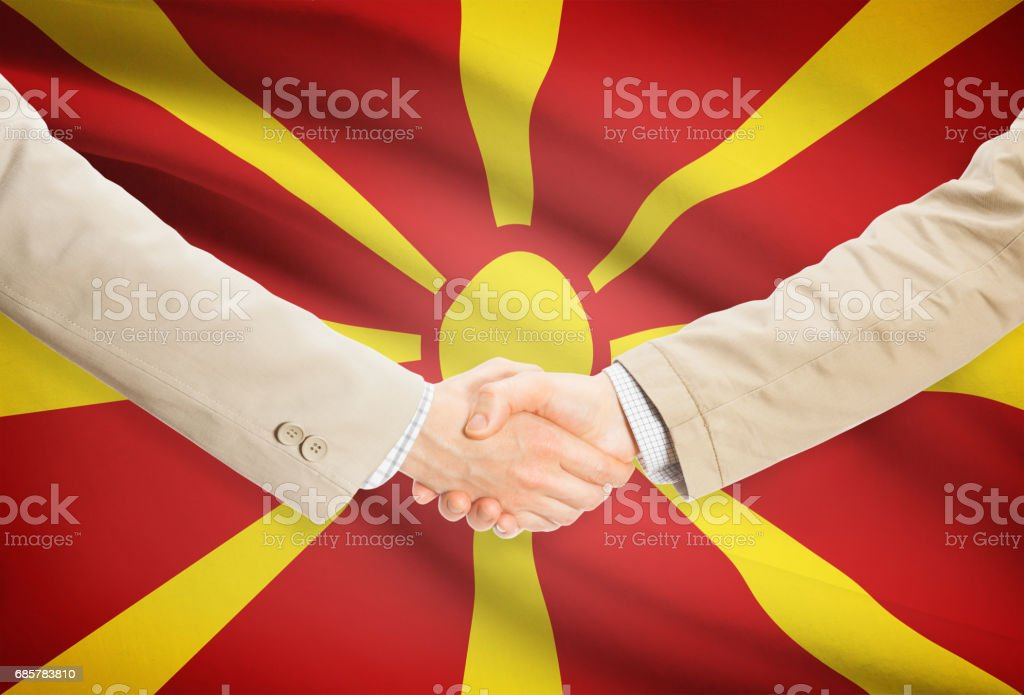 Businessmen handshake with flag on background - Republic of Macedonia royalty-free stock photo