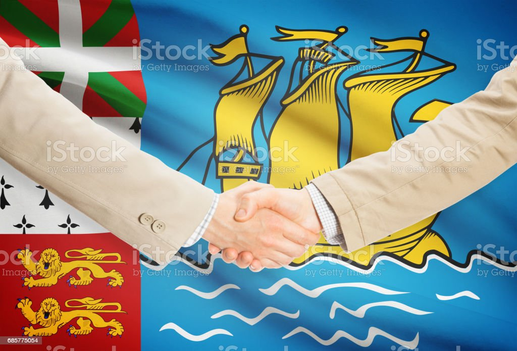 Businessmen handshake with flag on background - Saint-Pierre and Miquelon royalty-free stock photo
