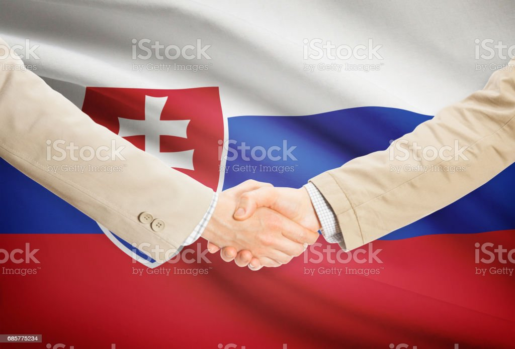 Businessmen handshake with flag on background - Slovakia royalty-free stock photo