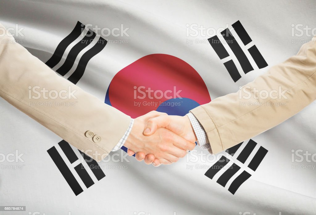 Businessmen handshake with flag on background - South Korea royalty-free stock photo