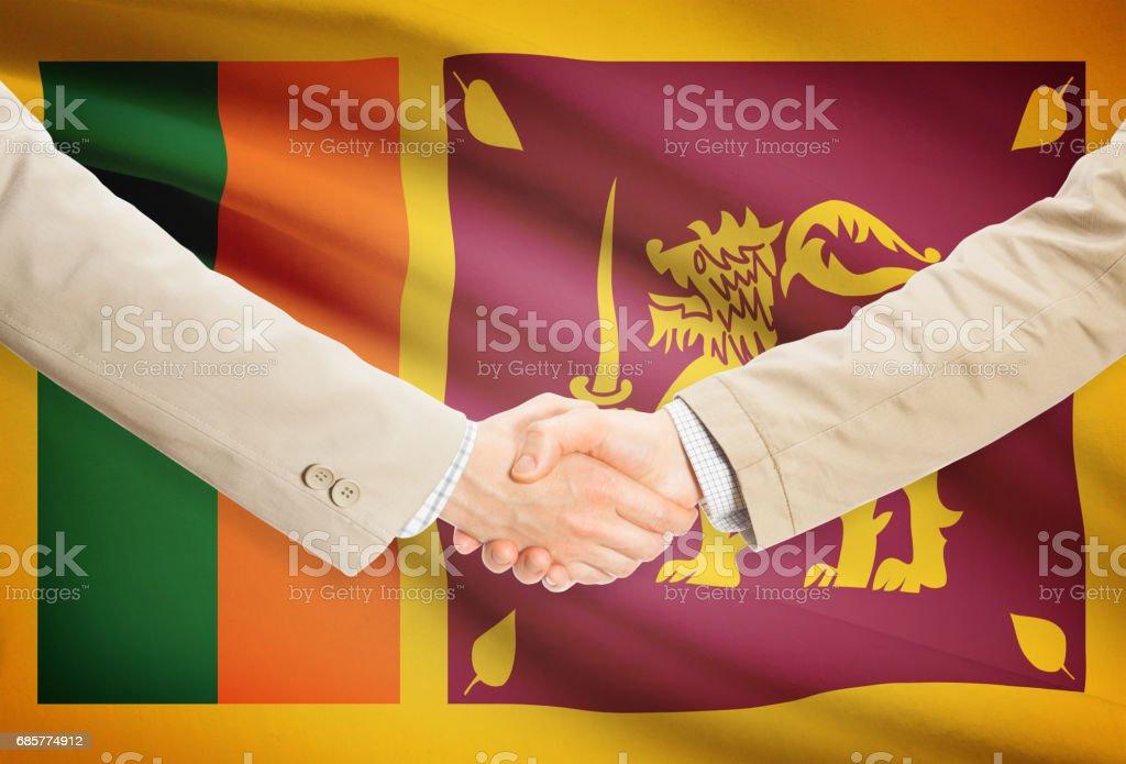Businessmen handshake with flag on background - Sri Lanka royalty-free stock photo