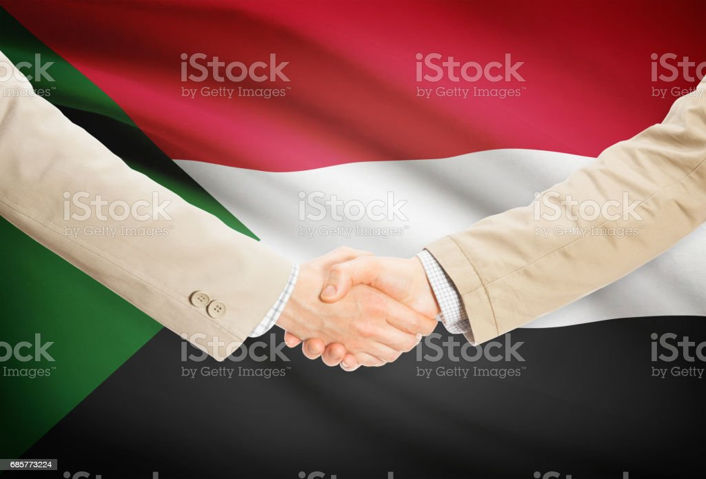 Businessmen handshake with flag on background - Sudan royalty-free stock photo