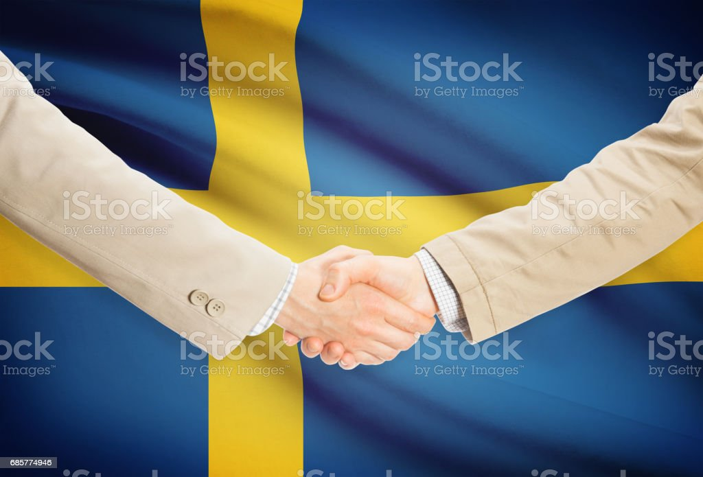 Businessmen handshake with flag on background - Sweden royalty-free stock photo
