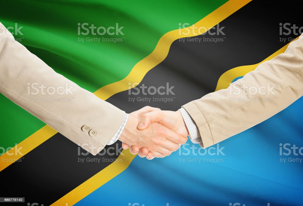 Businessmen handshake with flag on background - Tanzania royalty-free stock photo