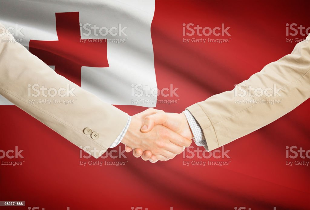Businessmen handshake with flag on background - Tonga royalty-free stock photo