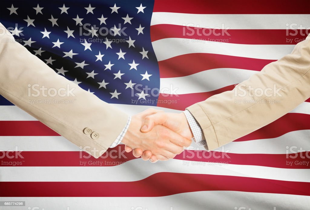 Businessmen handshake with flag on background - United States royalty-free stock photo
