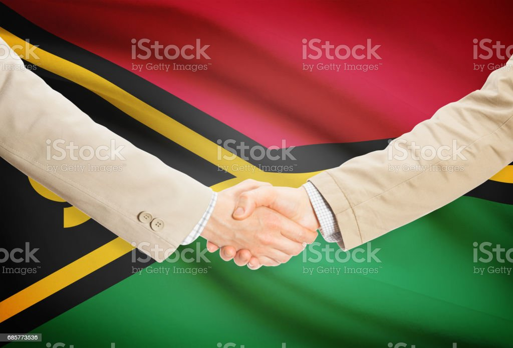 Businessmen handshake with flag on background - Vanuatu royalty-free stock photo