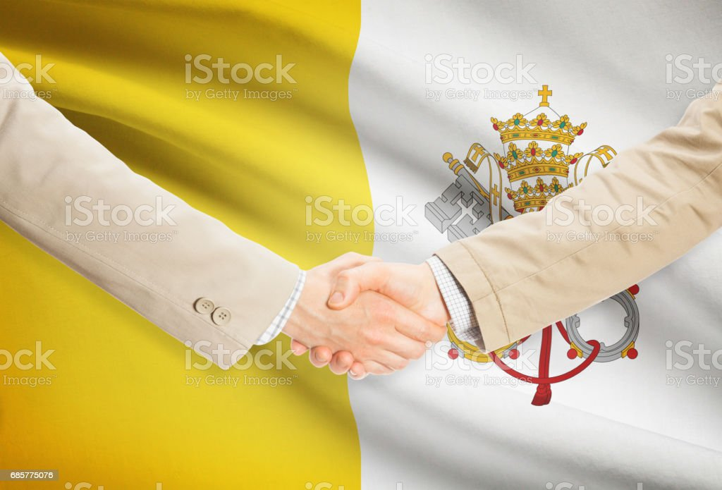 Businessmen handshake with flag on background - Vatican City royalty-free stock photo