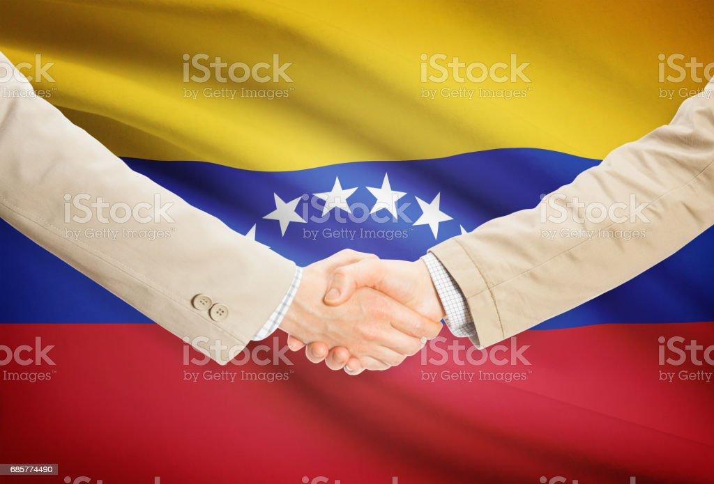Businessmen handshake with flag on background - Venezuela photo libre de droits