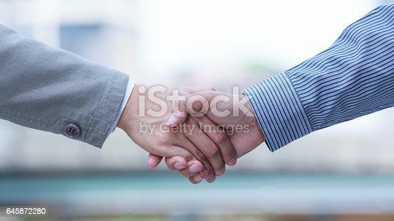 istock businessmen handshaking 645872280